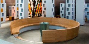 Bild zeigt die rund Bank aus Holz mit Taufstein in der Mitte